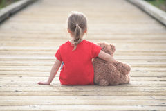 Little girl in a red dress waiting on a boardwalk hugging teddyb. Ear, view from behind Royalty Free Stock Photos