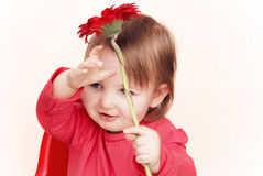 Little girl with red flower. Smiling toddler on a pale background holding a red flower above her head Stock Photos