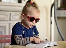 Red glasses.Little girl in red glasses reading a book. The little girl in red glasses ,with beads around her neck reading a book royalty free stock photo