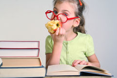 Little girl in red glasses bitten apple Royalty Free Stock Photos