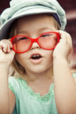 Little girl in red glasses and a cap Royalty Free Stock Image