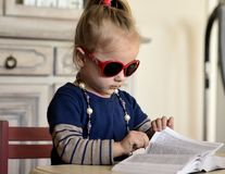 Book.Little girl in red glasses reading a book. The little girl in red glasses ,with beads around her neck reading a book stock photography