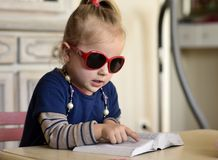Little girl in red glasses reading a book. The little girl in red glasses ,with beads around her neck reading a book Royalty Free Stock Photography