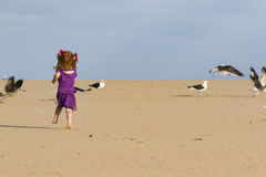 Little girl with red hair chasing birds. Young girl red hair chasing birds on beach royalty free stock image
