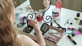 Little girl with red hair chooses eye shadow, looks in the mirror, makeup, face, fashion, style, cosmetics, close-up. Hands 4k stock video footage