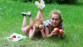Little girl with red hair and her mother play with apples on lawn in green summer park stock video