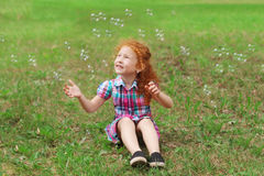 Little girl with red hair sits on grass and catches bubbles Royalty Free Stock Images