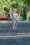 Little girl with red hair runs with windmill. Little girl with red hair in skirt runs with windmill in summer green park Royalty Free Stock Images