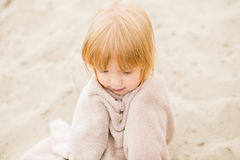 Little girl with red hair in a towel at the beach Royalty Free Stock Photo