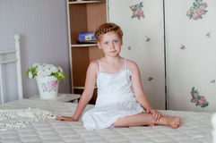 Little girl with red hair in a white dress  Stock Photo