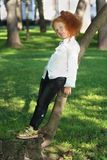 Little girl with red hair in white shirt poses near tree. In summer green park royalty free stock photography