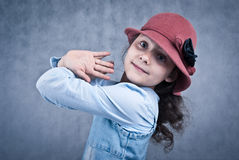 Little girl in red hat. Looking and smiling in front of grey background Stock Photos