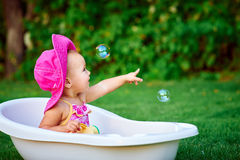 Little girl in a red hat bathed in the bath Stock Images