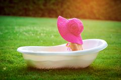 Little girl in a red hat bathed in the bath Royalty Free Stock Image