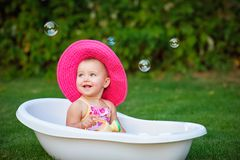 Little girl in a red hat bathed in the bath Royalty Free Stock Photos