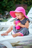 Little girl in a red hat drinking from a mug Royalty Free Stock Image