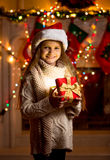 Little girl in red hat holding sparkling gift box Royalty Free Stock Photo