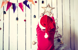 Little girl in red hat putting a star on top of christmas tree. In decorated room Stock Photo