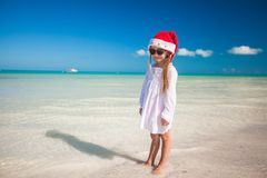 Little girl in red hat santa claus and sunglasses. On the exotic beach Royalty Free Stock Photo