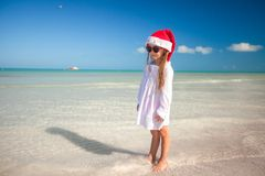 Little girl in red hat santa claus and sunglasses. On the exotic beach Royalty Free Stock Photography