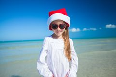 Little girl in red hat santa claus and sunglasses. On the exotic beach. This image has attached release Stock Photos