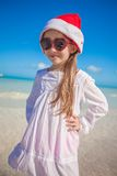 Little girl in red hat santa claus and sunglasses. On the exotic beach. This image has attached release Royalty Free Stock Image