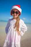 Little girl in red hat santa claus and sunglasses. On the exotic beach. This image has attached release Stock Image