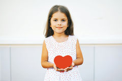 Little girl with red heart. Against wall Stock Photography