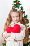 Little girl with red heart toy Stock Images