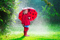 Little girl in red jacket playing in autumn rain. Little girl with red umbrella playing in the rain. Kids play outdoors by rainy weather in fall. Autumn outdoor Royalty Free Stock Photography