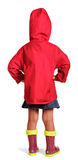 Little girl in red jacket, skirt, rubber boots standing isolated. Stock Photos