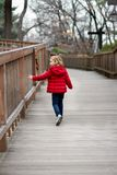 A little girl in a red jacket walks down the road touching the fence royalty free stock image
