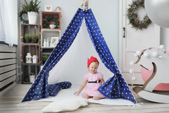 The little girl with red koronjq sits in a wigwam royalty free stock photo