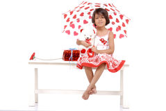 Little girl with red objects holding teddy bear Royalty Free Stock Photo