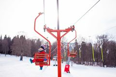 Child Girl On A Chair Ski Lift Going Uphill In The Mountains