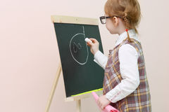 Little girl with red pigtails in glasses chalk draws Stock Images