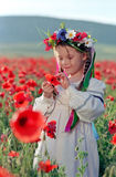 Little girl on red poppy field Royalty Free Stock Images