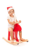 Little girl on red reindeer in studio Royalty Free Stock Photos