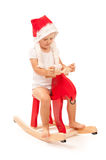 Little girl on red reindeer in studio Stock Photos