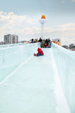 Little girl in red rolls to ice slide in Ice town Royalty Free Stock Photography