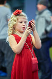 Little girl  with red rose in hair looks at cell phone. Little girl in red dress with red rose in her hair looks at red cell phone in her hands Royalty Free Stock Images
