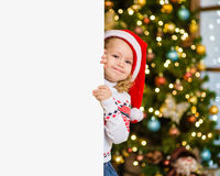 Little girl in red santa hat behind white board. Space for text Royalty Free Stock Image