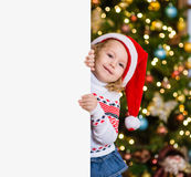 Little girl in red santa hat behind white board. Space for text Stock Photo