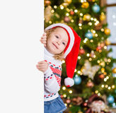 Little girl in red santa hat behind white board. Space for text Stock Images