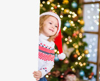Little girl in red santa hat behind white board. Space for text Royalty Free Stock Photography