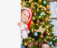 Little girl in red santa hat behind white board. Space for text Stock Image
