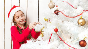 Little girl in red santa hat decorating new year tree. Little cute girl in red santa hat decorating new year tree Royalty Free Stock Photography