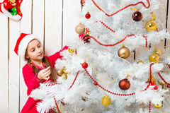 Little girl in red santa hat decorating new year tree. Little cute girl in red santa hat decorating new year tree Stock Photo