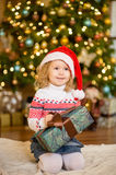 Little girl in red santa hat holding christmas gift box Royalty Free Stock Images
