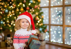 Little girl in red santa hat holding christmas gift box Royalty Free Stock Photos